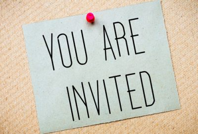 Recycled paper note pinned on cork board. You Are Invited Message. Concept Image